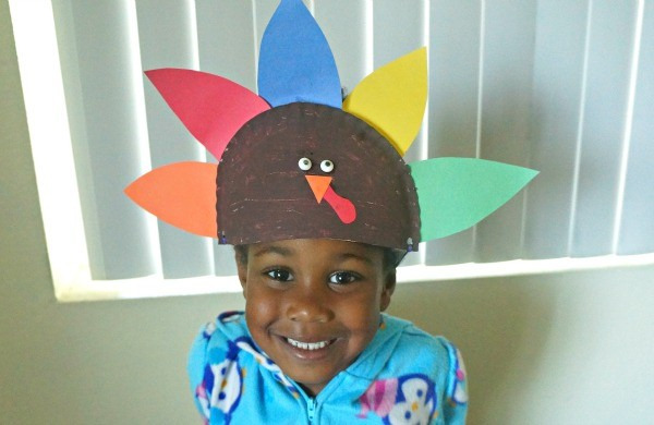 Girl wearing her paper plate Thanksgiving turkey hat craft